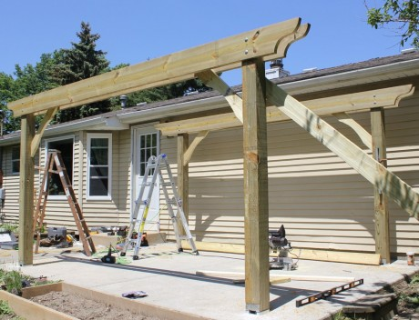 "Before installing the joists, we wanted to give the structure more stability, to prevent it from racking. (Having pergola parts raining down on you doesn't generally improve the festive party atmosphere—unless you're a personal injury attorney…). We cut 2X6's into pieces about 3' long, cutting 45º angles on the ends, and scribing and cutting a gracious Mediterranean curve onto each. (Okay, so maybe it was a stylish Buckeye curve). After pre-drilling, to avoid splitting the wood, and double-checking for plumb, we screwed them to the face of the post, holding them all to the same height, then to the headers, using 3"" exterior screws."