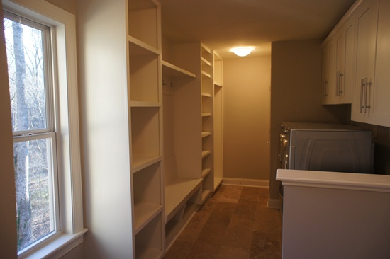 Combing the mudroom with the laundry room has the added benefit of allowing you sit and watch the dryer spin.