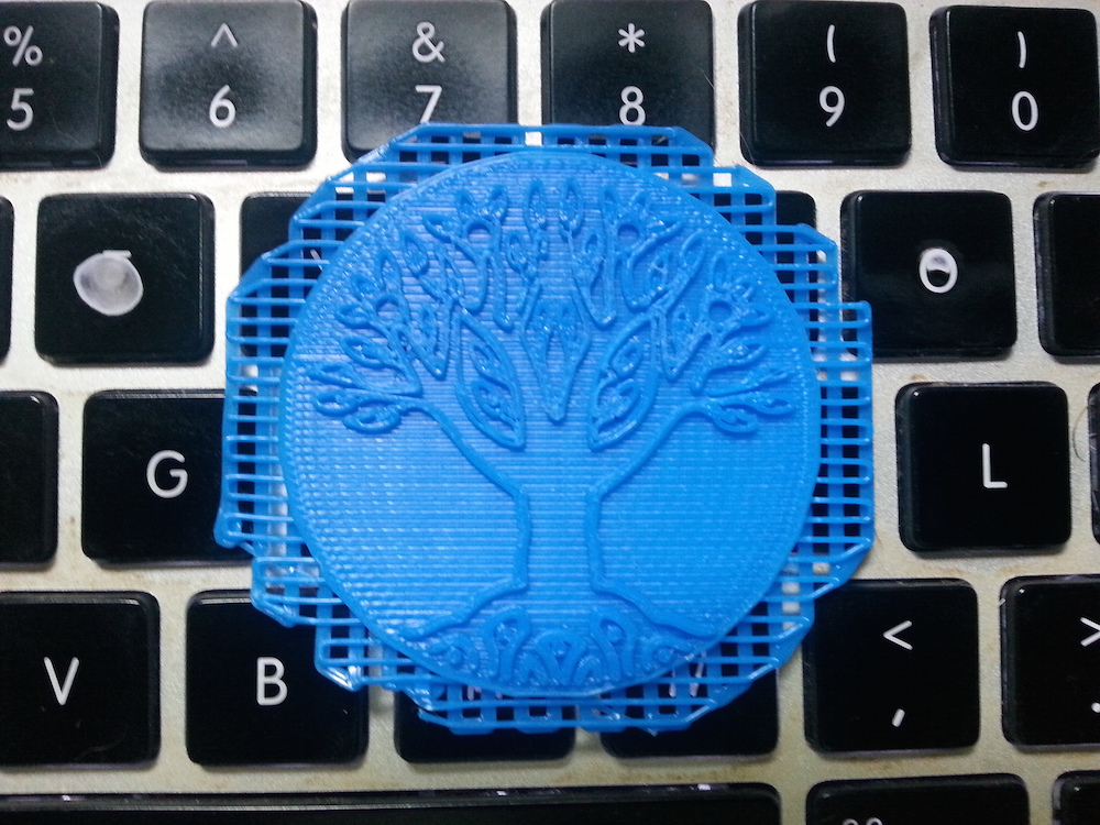 "Step 3: The medallion printed on a ""raft."" The raft is a mesh that helps thin parts remain flat while printing."
