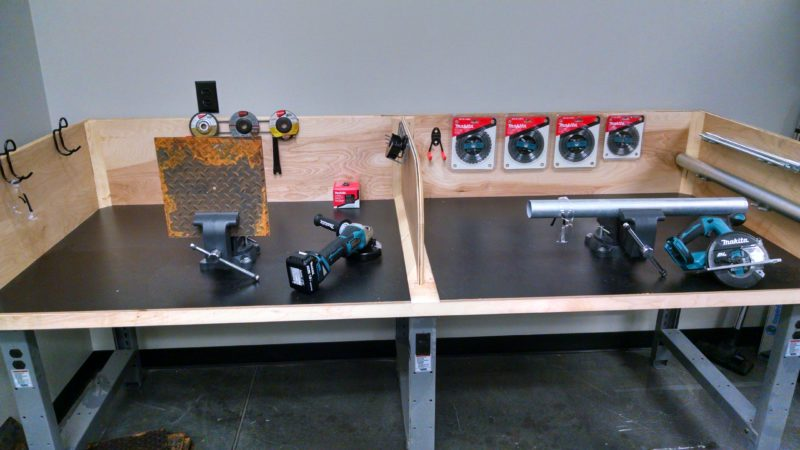 training center lab station with grinders and steel tubing.