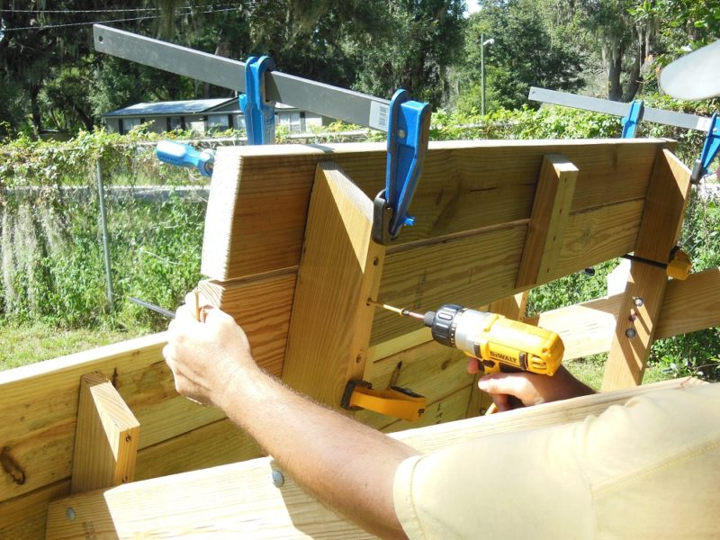 Screwing the bench slats in place.