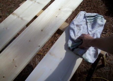 Rub it in wood grains using a circular motion, and then wipe it off going with the grain